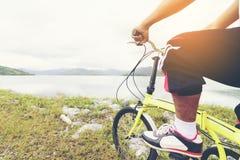Езда человека азиатская велосипед и вид на озеро стоковые фото