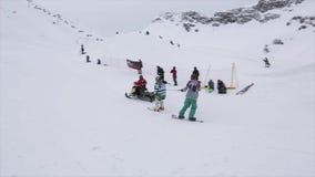 Езда лыжников на владении снегохода на веревочке лыжа курорта смелости горы снежные акции видеоматериалы