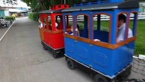 Езда людей в привлекательностях парка в поезде видеоматериал