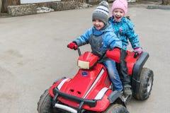Езда ` s детей девушки мальчика на двойном велосипеде квада Они одеты в брюках, куртках и крышках стоковые изображения