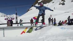 Езда Snowboarder на железном следе лыжа курорта смелости день солнечный весьма спорт акции видеоматериалы