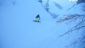 Езда 2 snowboarders вокруг снежного леса сток-видео