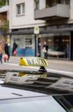 Ездите на такси клиенты знака ждать в городе с defocused pedestria Стоковые Изображения RF
