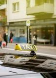 Ездите на такси клиенты знака ждать в городе с defocused pedestria Стоковое Изображение