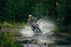 Езды гонщика Motocross через лужицу Стоковые Изображения RF