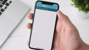 Екатеринбург, Россия - 3-ье октября 2018: Человек используя Амазонку app на smartphone iPhone x, просматривая для camcoder видеоматериал