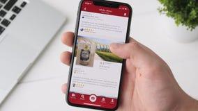 Екатеринбург, Россия - 3-ье октября 2018: Человек используя вино app на smartphone iPhone x, просматривая для бутылки вина видеоматериал