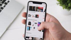 Екатеринбург, Россия - 3-ье октября 2018: Человек используя Aliexpress app на smartphone iPhone x, просматривая через страницу сток-видео