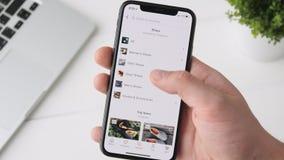 Екатеринбург, Россия - 3-ье октября 2018: Человек используя Etsy app на smartphone iPhone x, просматривая через страницу видеоматериал
