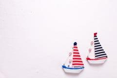 2 декоративных деревянных шлюпки игрушек на текстурированной белой предпосылке Стоковое Фото