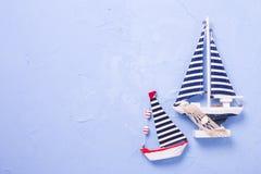 2 декоративных деревянных шлюпки игрушек на текстурированной голубой предпосылке Стоковые Изображения RF