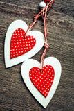 2 декоративных красных и белых сердца на деревянной предпосылке Стоковые Изображения RF
