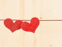 2 декоративных красных сердца вися на деревянной предпосылке, концепции дня валентинки Стоковое Изображение