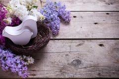 2 декоративных птицы в гнезде и свежих ароматичных цветках сирени Стоковая Фотография
