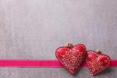 2 декоративных сердца и ленты на серой предпосылке шифера Стоковая Фотография