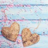 2 декоративных сердца и лепестка розовой Сакуры цветут на bl Стоковые Изображения