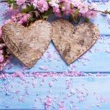 2 декоративных сердца и розовой Сакура цветут на голубом деревянном b Стоковые Изображения RF