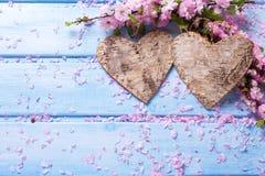 2 декоративных сердца и розовой Сакура цветут на голубом деревянном b Стоковое фото RF