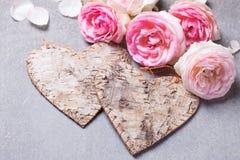 2 декоративных сердца и свежих розовых розы на серой предпосылке Стоковое Изображение RF