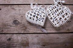 2 декоративных сердца на винтажной деревянной предпосылке Стоковая Фотография