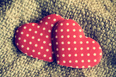 2 декоративных сердца на предпосылке дерюги Стоковая Фотография