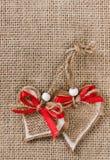 2 декоративных сердца на предпосылке мешковины Стоковое Изображение