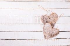 2 декоративных сердца на предпосылке покрашенной белизной деревянной Стоковое Фото