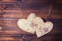 2 декоративных сердца на предпосылке покрашенной темнотой деревянной Стоковые Фотографии RF
