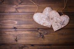 2 декоративных сердца на предпосылке покрашенной темнотой деревянной Стоковые Изображения