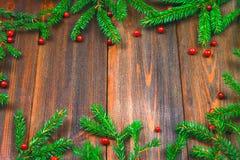 Елевые ветви с красными ягодами на деревянном столе скопируйте космос стоковая фотография rf