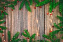 Елевые ветви с красными ягодами на деревянном столе скопируйте космос стоковые изображения