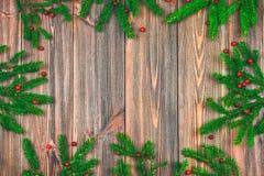 Елевые ветви с красными ягодами на деревянном столе скопируйте космос стоковое изображение