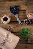 Ель, конус сосны и оборачивая материалы на деревянном столе Стоковое Изображение