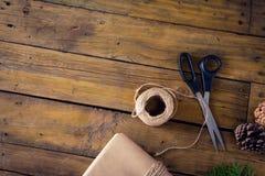 Ель, конус сосны и оборачивая материалы на деревянном столе Стоковые Фотографии RF