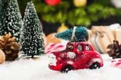 Ель нося миниатюрного красного автомобиля на предпосылке рождества Стоковое Изображение RF
