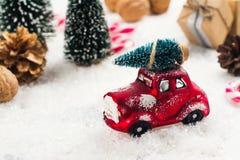 Ель нося миниатюрного красного автомобиля на предпосылке рождества Стоковые Фотографии RF