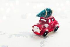 Ель нося миниатюрного красного автомобиля на предпосылке рождества Стоковое Фото