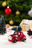 Ель нося миниатюрного красного автомобиля на предпосылке рождества Стоковое Изображение