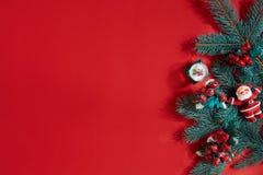 Ель разветвляет граница на красной предпосылке, хорошей для фона рождества Стоковое Фото