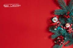 Ель разветвляет граница на красной предпосылке, хорошей для фона рождества Надпись - с Рождеством Христовым Стоковые Изображения