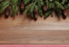 Ель разветвляет с конусами на деревянной предпосылке Стоковые Изображения