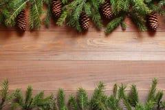 Ель разветвляет с конусами на деревянной предпосылке Стоковые Фото