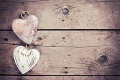 2 деревенских декоративных сердца на винтажной деревянной предпосылке Стоковые Изображения RF