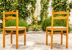 2 деревянное и плетеные стулья в славном и дворе Стоковые Фото