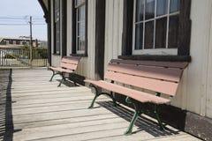 2 деревянной скамьи старым зданием Стоковое Изображение RF