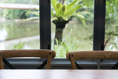 деревянные таблица и стул в столовой около окна с озером Стоковая Фотография RF