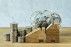 деревянный миниатюрный дом с стогом монеток и монеток в стеклянном ja Стоковое Изображение