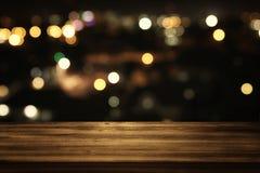 деревянный стол перед запачканными конспектом светами ресторана стоковые фотографии rf