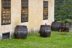 4 деревянных бочонка стоя в задворк старого дома На заднем плане несколько ладоней canariensis Феникса Стоковое Фото