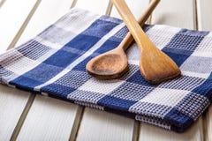 2 деревянных варя ложки на голубом полотенце на деревянном столе Стоковое Фото